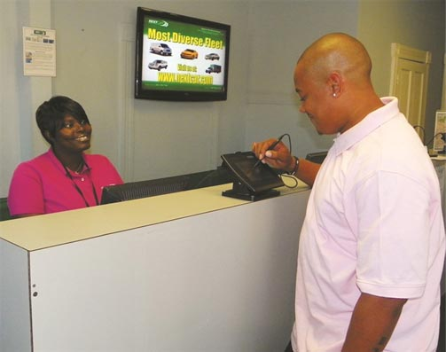 A NextCar customer uses the e-signature pad to review and approve his rental agreement. Photo credit: NextCar